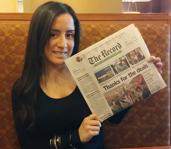 The Class of 2009 graduate holds up her front page story, which recently ran in The Record.