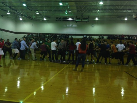 The male faculty challenges the senior boys to a tug of war.