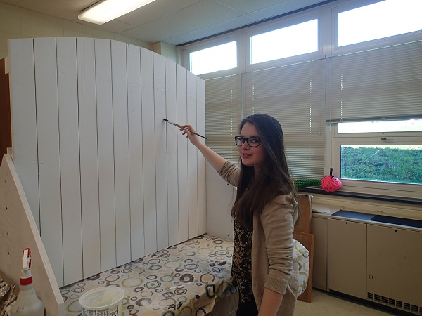 Sophomore Claudia Kruk begins to paint the fence.