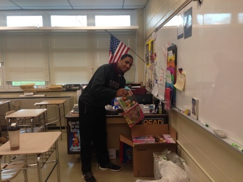 Senior Rafael Mercedes drops off toys in the designated bin.