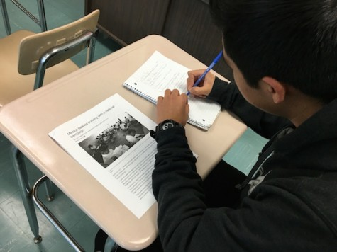 A Becton student is practicing his reading comprehension skills by reading a non-fiction article on the effects of bullying.