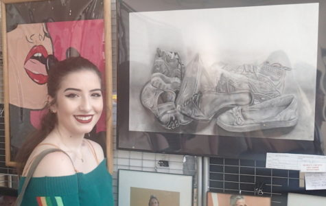 Senior Gina Beneduci proudly stands next to her award-winning artwork.