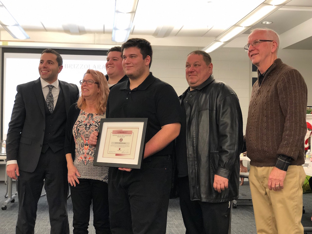 Senior David Brizzolara receives the Act of Kindness Award at the December board of education meeting alongside his family, Dr. Sforza and Becton BOE President Mr. Robert Anderson.