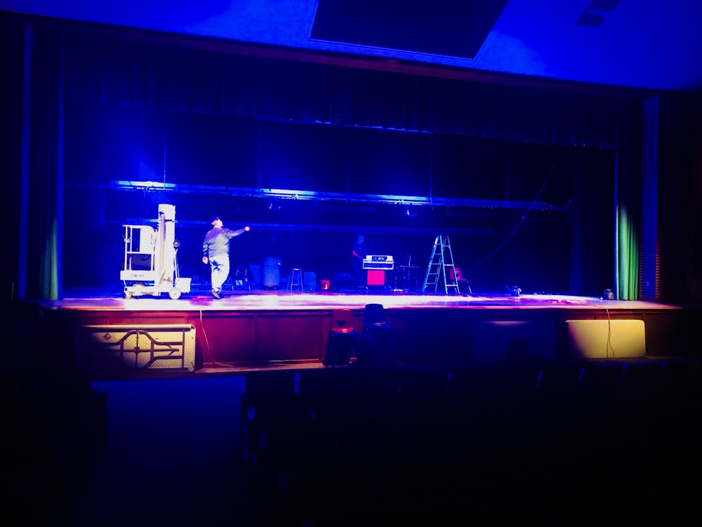 Mr. Phil Caputo, Supervisor of Building and Grounds, tests out the stage lighting with the high school's custodial staff.