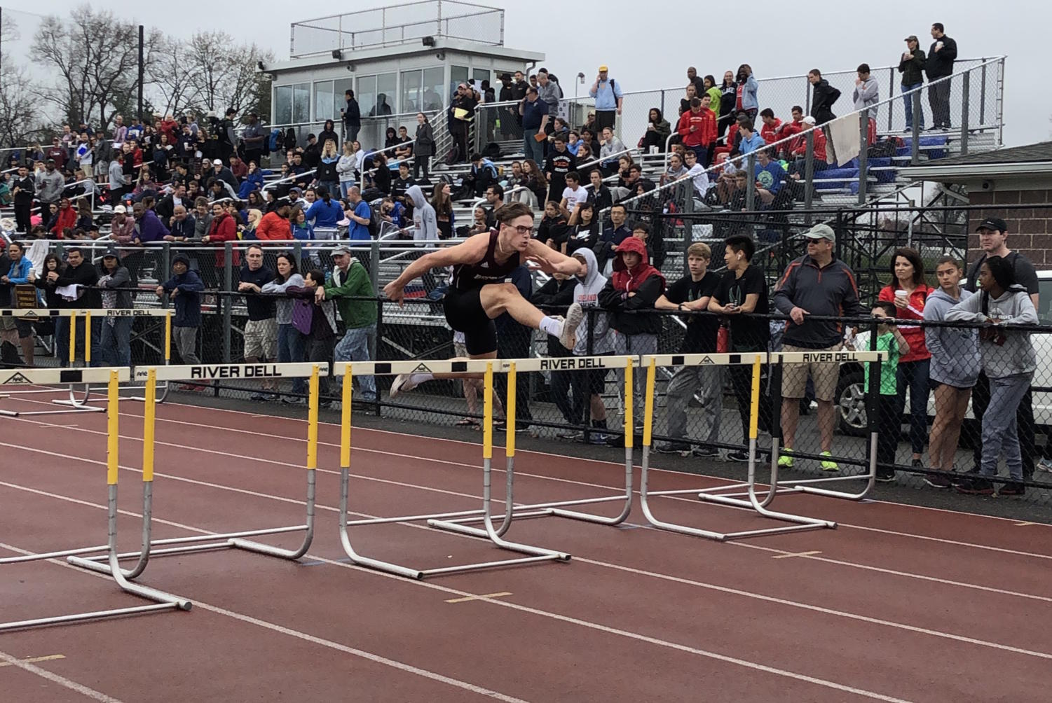Onlookers watch Stephen Henke hurdle his way to victory at the latest track meet.