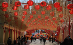 Lanterns hang in the streets, as a celebration of Lunar New Year, while those below practice social-distancing.
