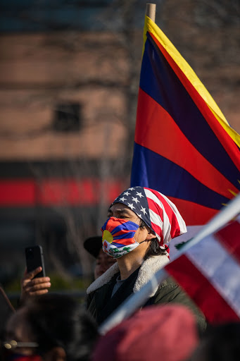 Capturing what it truly means to be a Tibetan American, the man observes the speakers at the demonstration of the peaceful protest outside the Chinese Consulate in New York City, NY, USA.